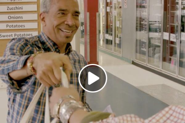 Man giving customer a grocery bag.