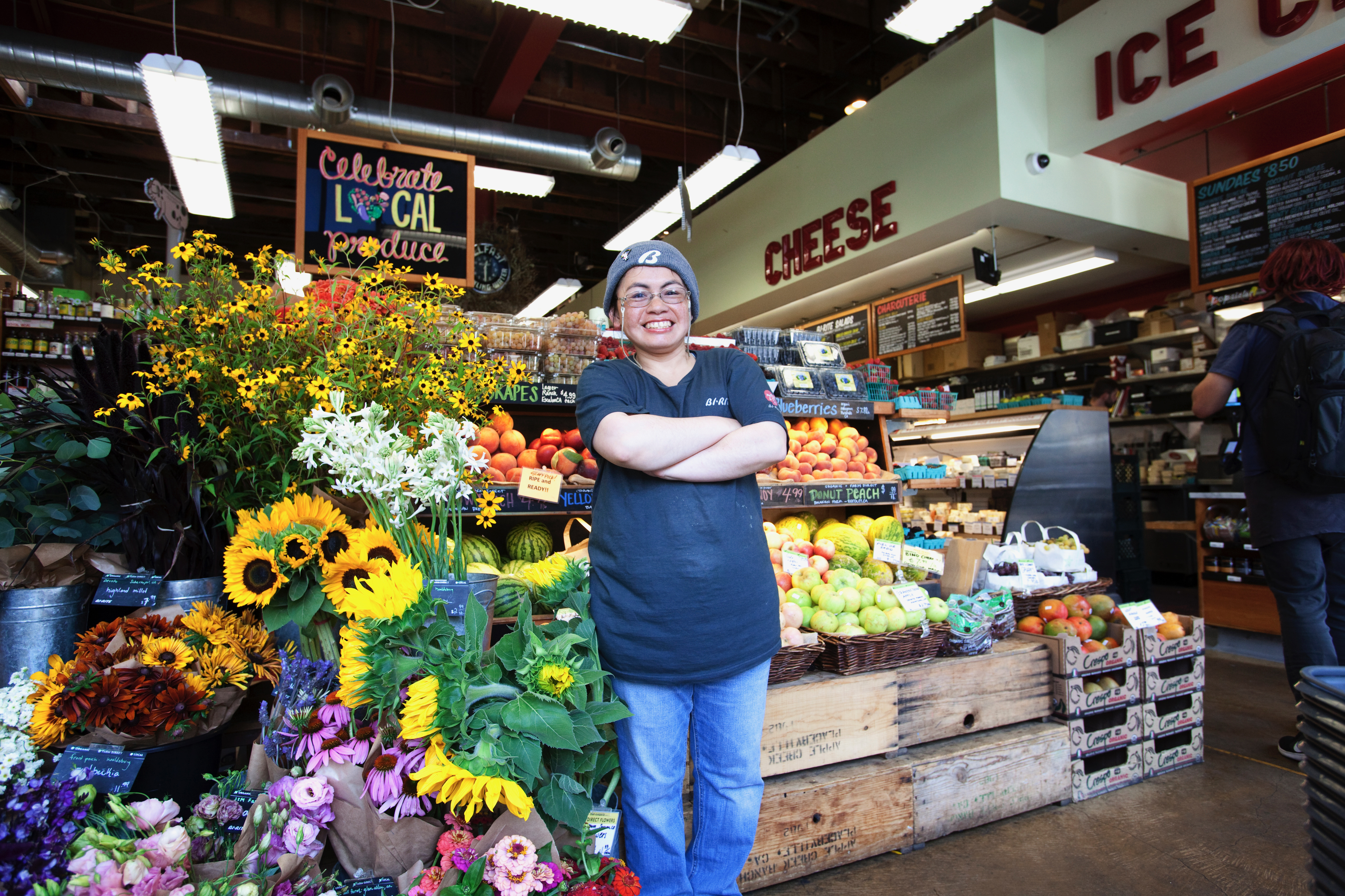 Karla, a Worklink client, posing at work in front of a fruit stand
