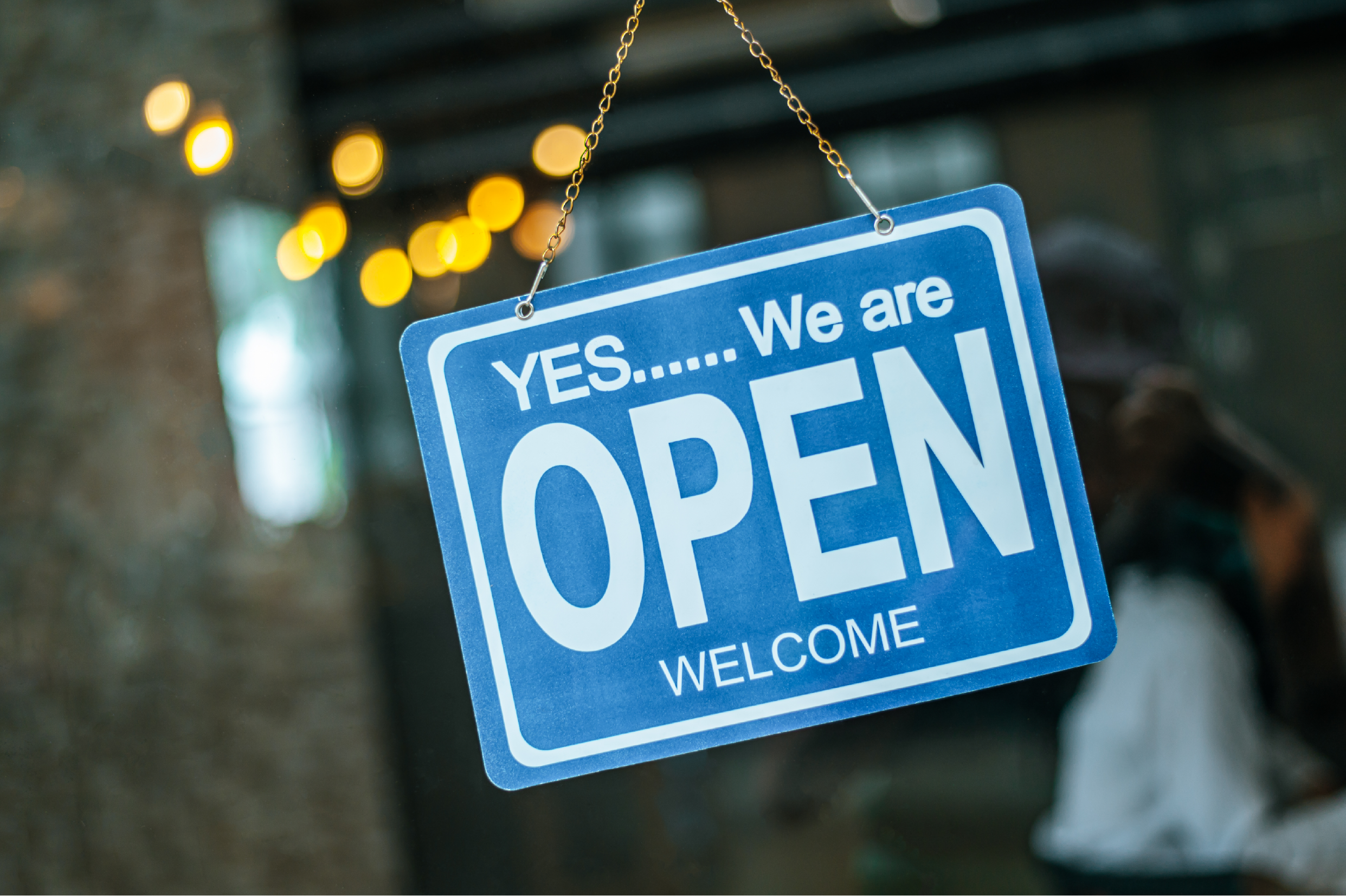 Store front with sign: Yes...we are open. Welcome